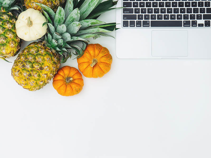 Pineapple next to a laptop