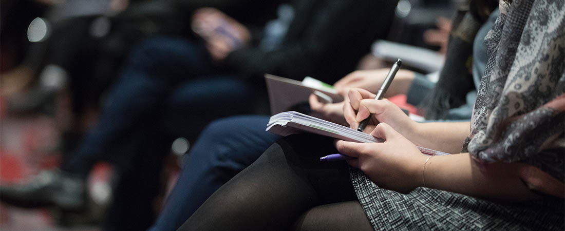person writing notes at an event